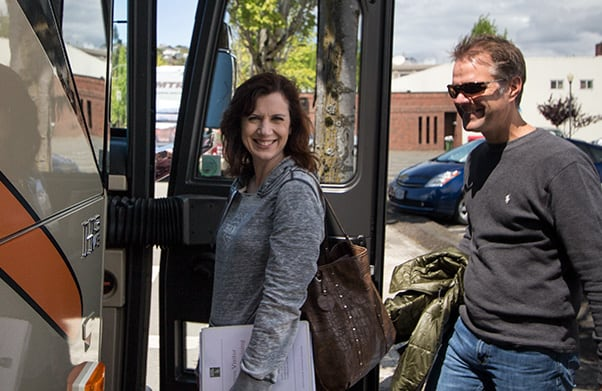 Woman and man smiling as they enter a motorcoach bus