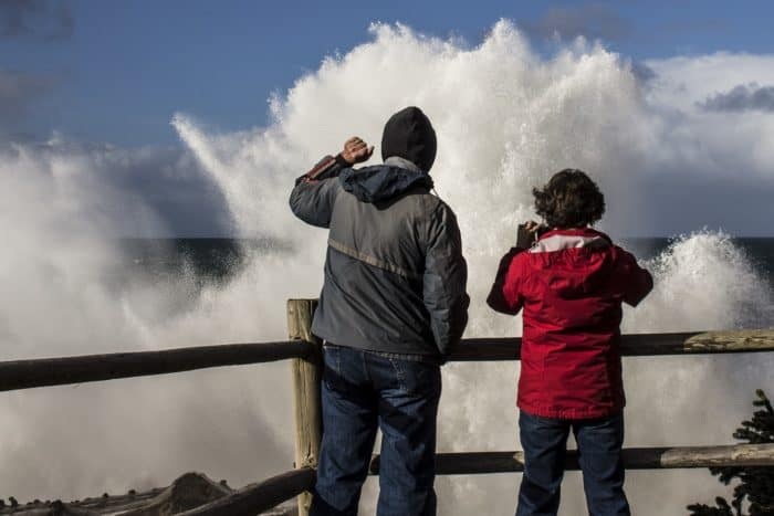 A couple watching dramatic waves crash against the Coos Bay, Oregon shore